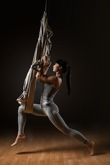 Девушка практикует воздушную йогу растяжения