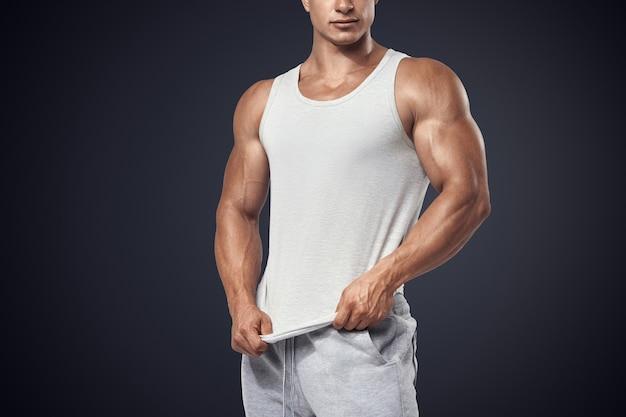 Молодой культурист в белой футболке без рукавов