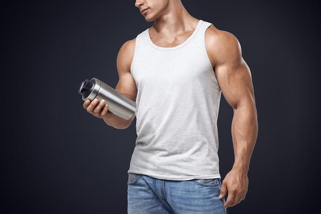 プロテインシェークボトルを保持している筋肉フィットネス男性