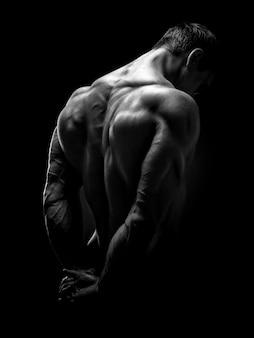 Красивый мускулистый культурист обернулся