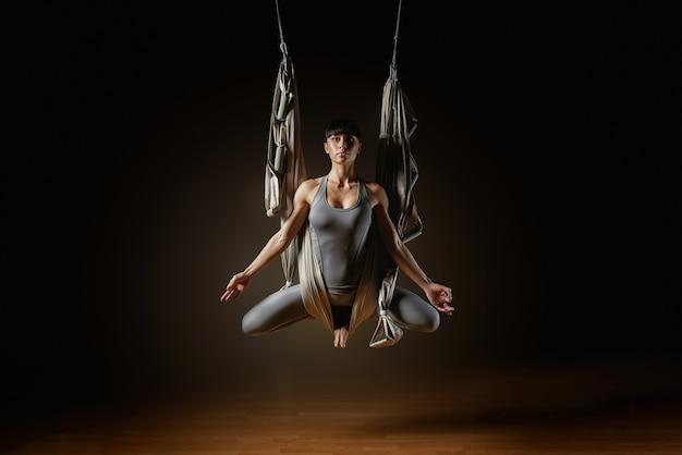 Молодая женщина практикует воздушный гамак йоги