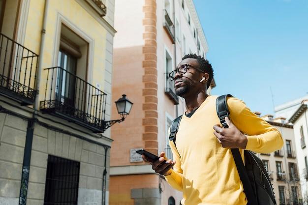 Потерянный туристический человек со смартфоном в городе мадрид