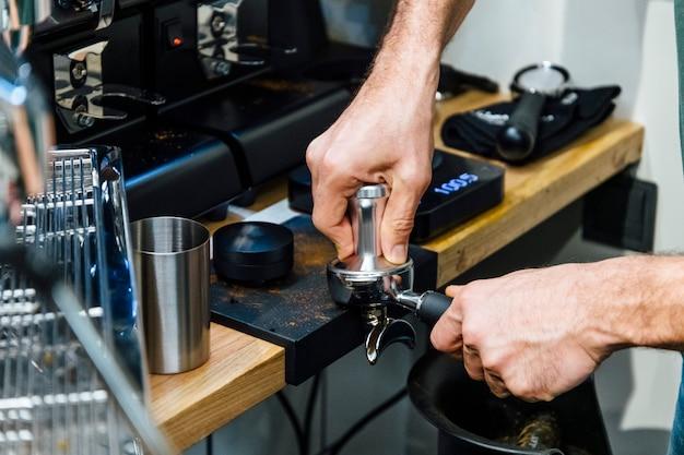 Бариста отжимает кофе в портафильтр