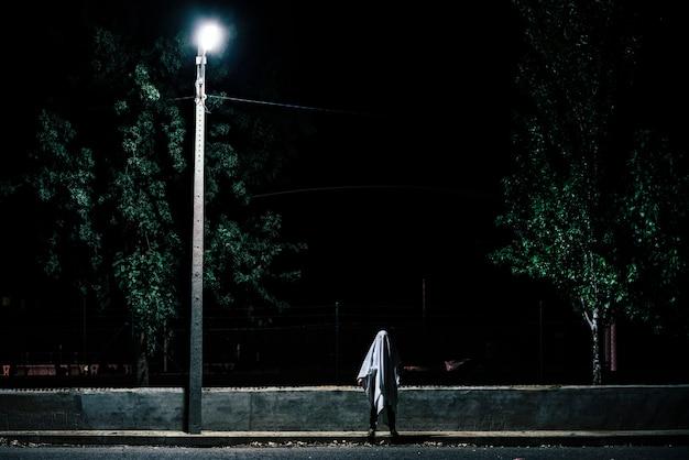Призрак в сумерках на дороге при слабом освещении.