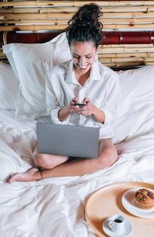 電話とベッドでノートパソコンのきれいな女性