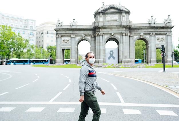 Человек идет по городу мадрид с маской