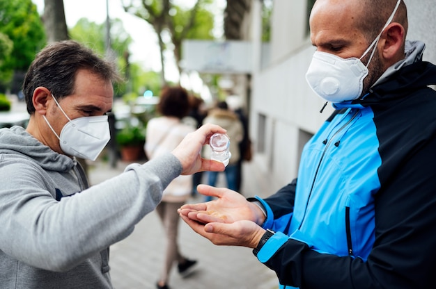 Двое мужчин дезинфицируют руки на улице