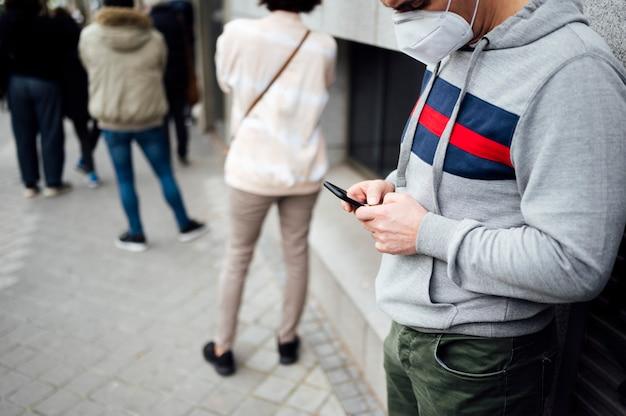Человек с помощью смартфона в ряд людей, ожидающих