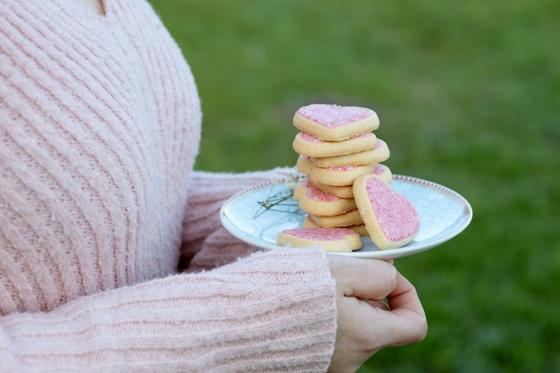 Девушка держит тарелку с розовым сердцем в форме печенья