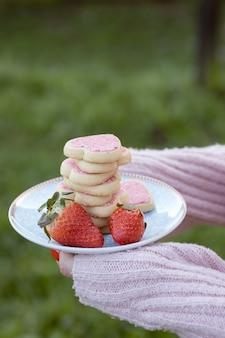 Девушка держит тарелку с розовым сердцем в форме печенья в сопровождении клубники