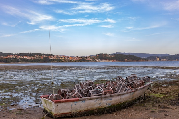 ガリシアのコンバロビーチで釣り道具がいっぱいの小さな放棄されたボート