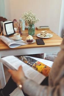 さまざまなデザートとテーブルの前で雑誌を読んでいる女の子