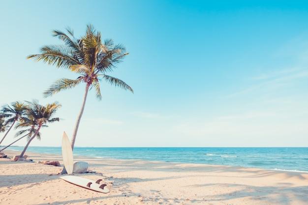 夏の熱帯のビーチでヤシの木とヴィンテージサーフボード。ヴィンテージ色調