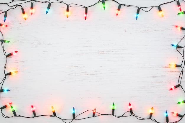 白い木の上にクリスマスライトバルブフレームの装飾。メリークリスマスと新年の休日