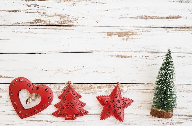 Рождественские миниатюрные дерево, рождественские украшения и украшения на фоне белого дерева.