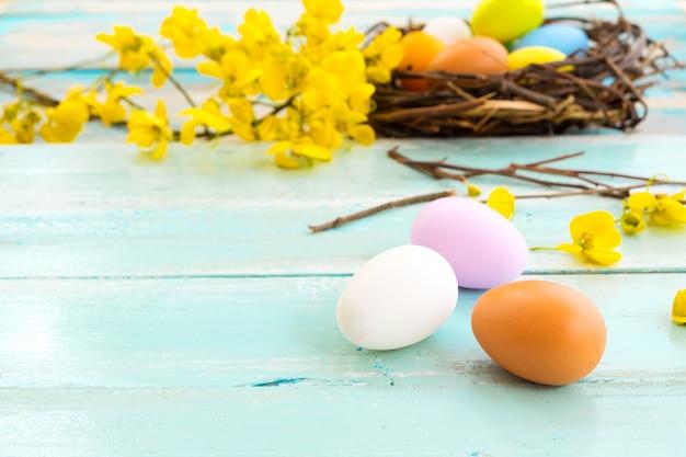 素朴な木製の板の背景に花と巣でカラフルなイースターエッグ