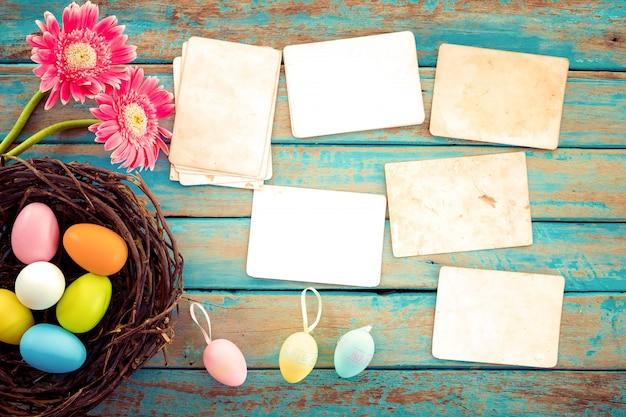 カラフルなイースターエッグの花と木のテーブルに空の古い紙の写真アルバムの巣