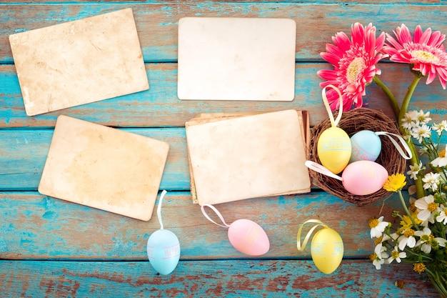 花と木のテーブルに空の古い紙のフォトアルバムと巣のイースターエッグ
