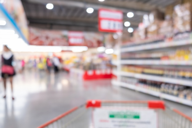 抽象的なスーパーマーケットの中の背景をぼかし。カートとスーパーマーケットのコンセプトで買い物。