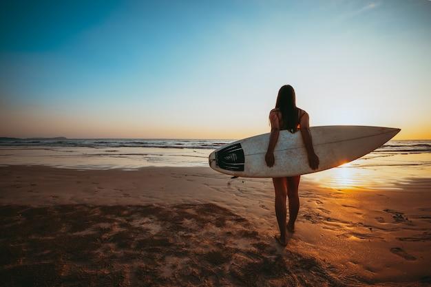 ビキニのサーファー女性はサーフィンに行きます。夕暮れ時のビーチのサーフボードと美しいセクシーな女性のシルエット。