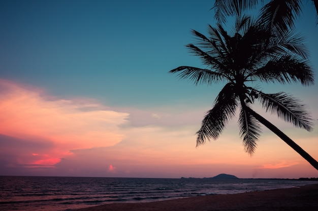 日没の夕暮れ時に熱帯のビーチのシルエット。日没時の夏のビーチとヤシの木の海の絵。