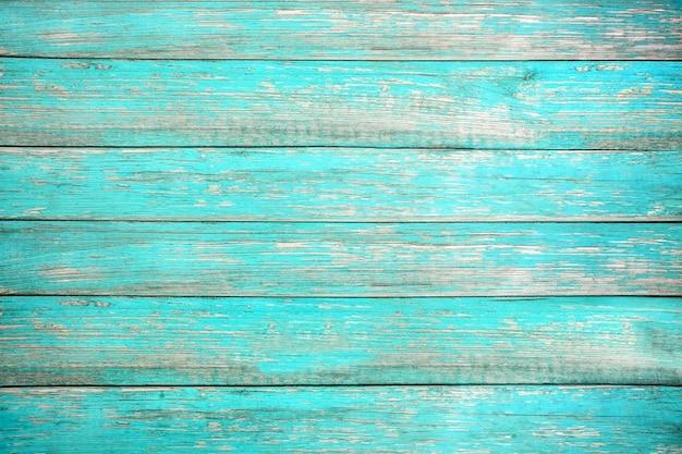 ターコイズブルーまたは青い海の色で塗られた古い風化した木の板。
