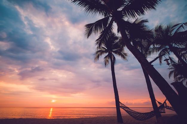 日没の夕暮れ時に熱帯のビーチのシルエット。