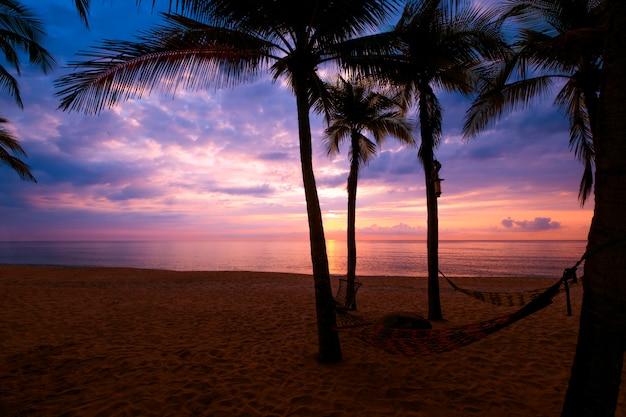 日没の夕暮れ時に熱帯のビーチのシルエット