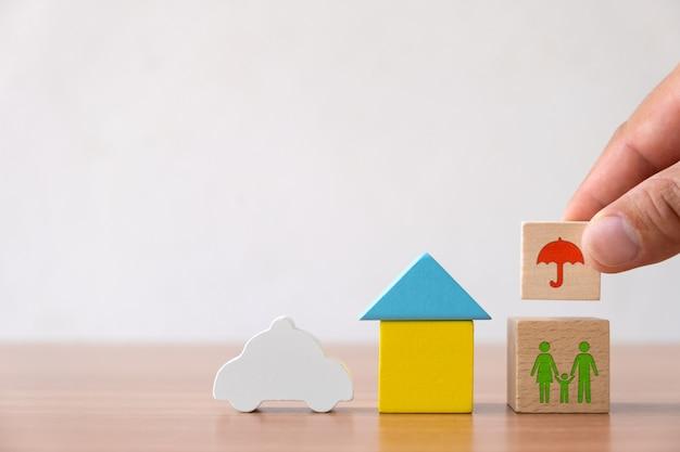 Страхование и инвестиционная концепция здоровья, жизни, несчастных случаев и путешествий. рука выбрала деревянный блок с темой страхования, дом, семья, автомобиль