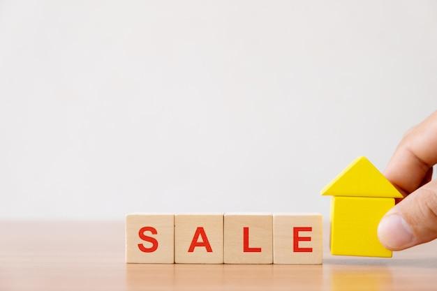 不動産投資と住宅ローンの金融の概念。 「販売」という言葉で木造住宅と木製キューブブロックを保持している手。