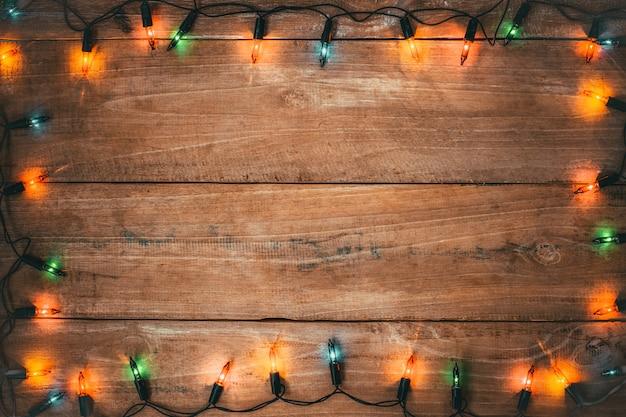 古い木の板にビンテージのクリスマスライト電球装飾。メリークリスマスと新年の休日の背景。