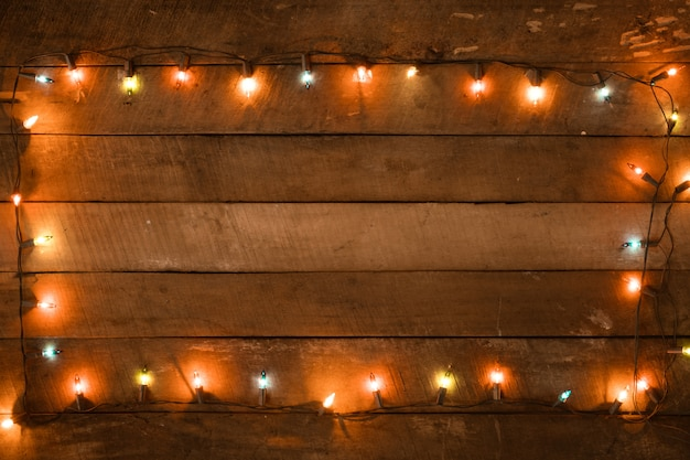 Рождественские огни украшения лампы на старой деревянной доске