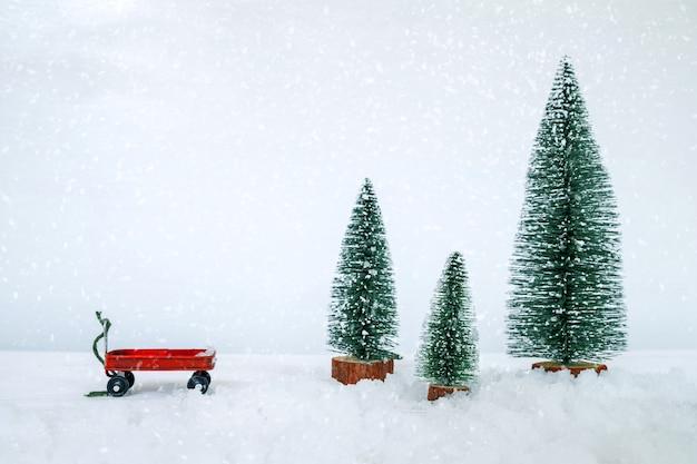 ヴィンテージメリークリスマスはがき背景雪に覆われた冬の森のミニチュアクリスマスツリー。