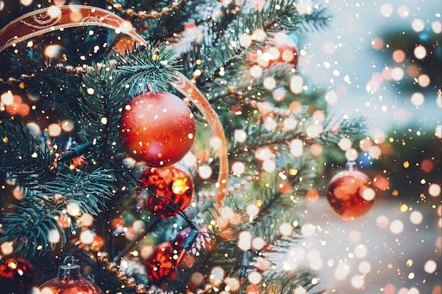 赤いボールの飾りと装飾、輝きのクリスマスツリー。クリスマスと新年の休日の背景。ヴィンテージ色のトーン。