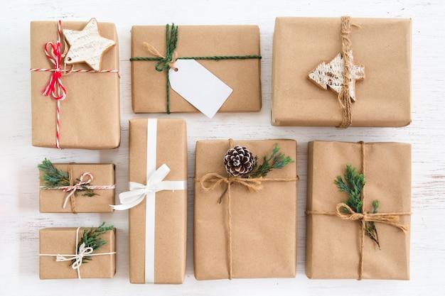 メリークリスマスと年末年始のタグを持つクリスマス素朴なプレゼントギフトボックスコレクション。上からの眺め。創造的なフラットレイアウトとトップビューのコンポジションデザイン。