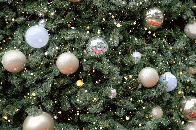 金のボールの飾りと装飾、輝きの光とビンテージのクリスマスツリー。クリスマスと新年の休日の背景。ヴィンテージ色のトーン。