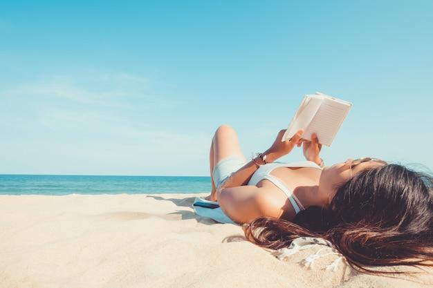 Молодая женщина, лежа на тропическом пляже