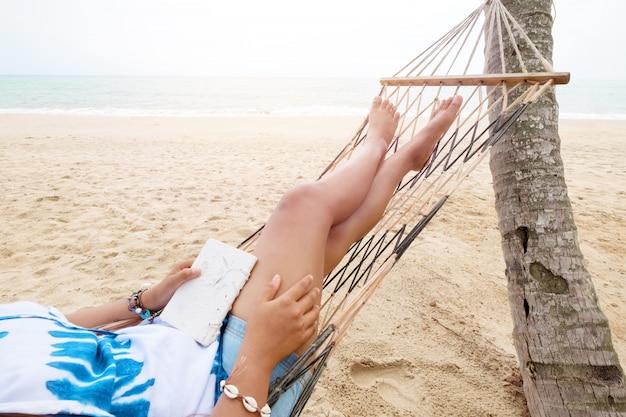 美しい日焼けしたセクシーな女性は日光浴し、リラックスし、熱帯の砂浜でハンモックで本を読みます