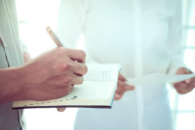 Женщины врач и мужчины доктор, пишущий блокнот, обсуждая информацию о профиле пациента в больнице.