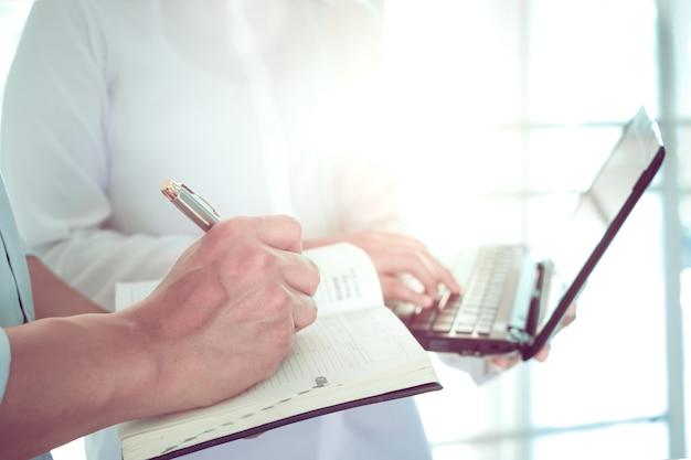 Женщины-врач с ноутбуком и мужчина-врач, пишущая записную книжку, обсуждая информацию о профиле пациента в больнице.