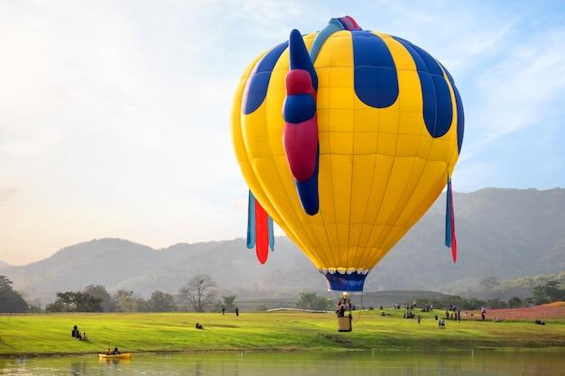 Фантастический воздушный шар, летящий на склоне холма. концепция путешествий и авиаперевозок - карнавал на воздушном шаре в таиланде
