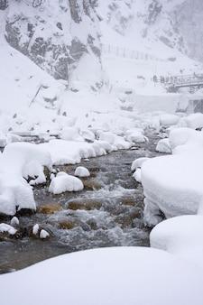 白い雪が空と冬の雪の嵐の背景の下に座って雪猿と凍る川の山と石を覆った