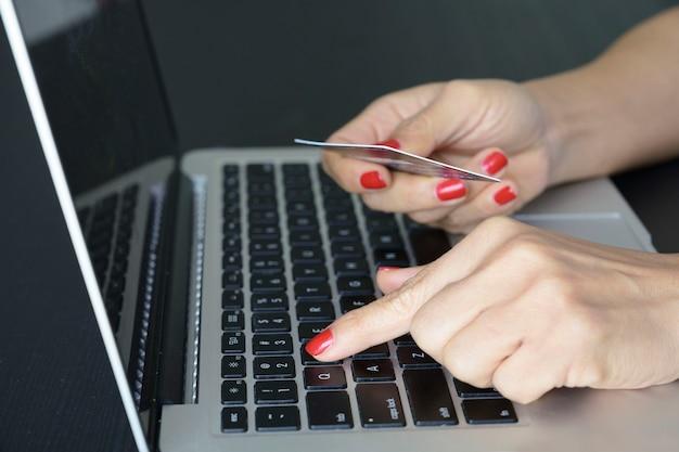 クローズアップ女性手クレジットカード、オンラインショッピング、金融の概念を保持しているコンピューターのキーボードで入力します。