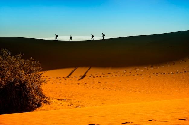 日光と青い空の上に歩いている人を認識できないシルエットと砂丘テクスチャの背景、