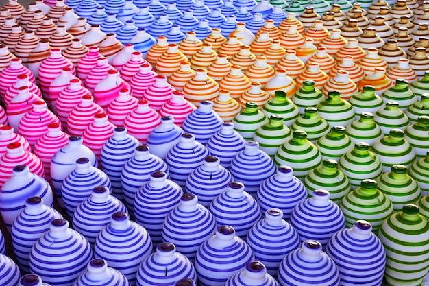 多くの色のカラフルな伝統的な手作りの粘土セラミック陶器をラインの背景にまとめ、