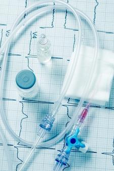 Внутривенная капельница на электрокардиограмме, лекарственное средство на вену, иглы