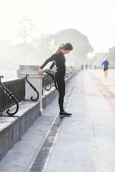 マドリードでフィットネスの前にストレッチする女性。スポーツ