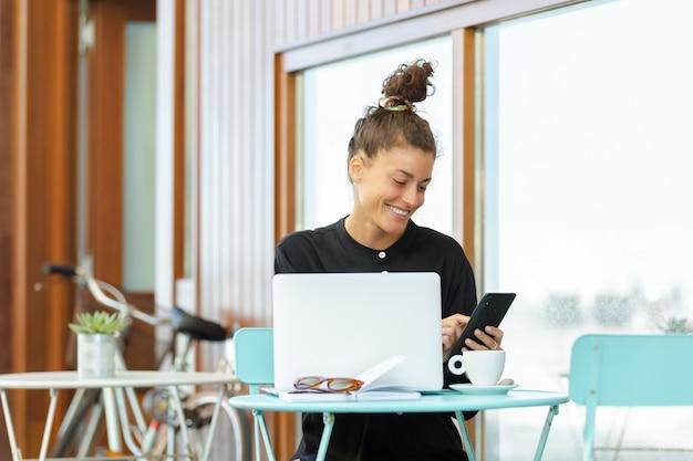 Работающая женщина на террасе бара, глядя на мобильный во время работы с ноутбуком и кофе.
