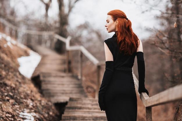 Яркая девушка с длинными рыжими волосами в черной одежде. женщина в черном платье и длинные черные перчатки позирует на зимней, осенней природы.