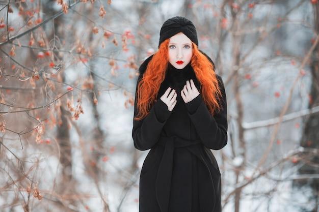 冬の森の上の毛皮の黒いコートに赤い髪の女性。